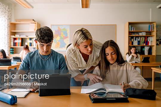 Female teacher teaching teenage girl on book in classroom - p426m2298666 by Maskot