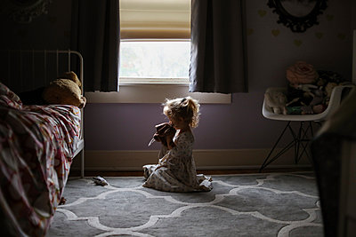 Side view of girl playing while sitting on carpet against window in bedroom - p1166m1554390 by Cavan Images