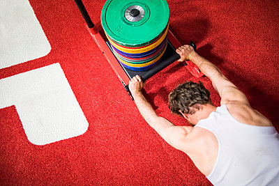 high angle of fit man pushing weight sled - p1166m2147278 by Cavan Images