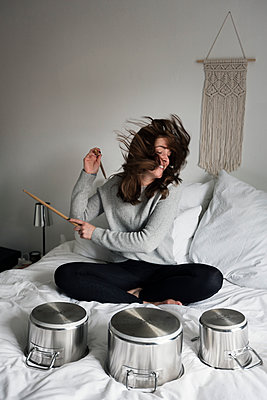 Woman playing pots and pans drum kit on her bed - p1515m2182091 by Daniel K.B. Schmidt