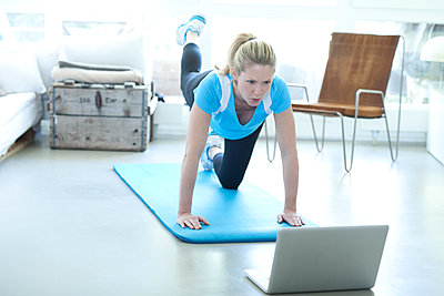 Woman looking at laptop exercising on gym mat in living room - p300m1188755 by Roman Märzinger