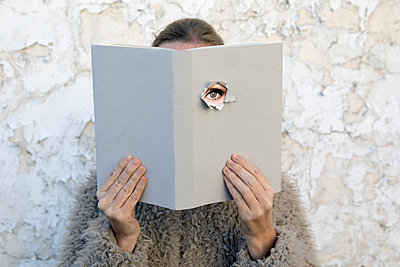 Woman covering face with book, reading poetry, eye looking through cover - p300m1581012 von Petra Stockhausen