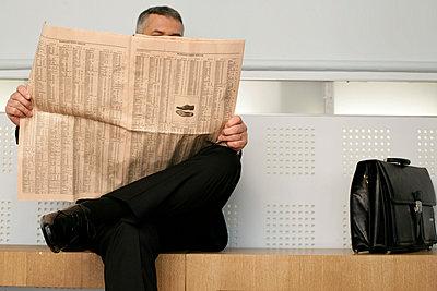 Lederne Aktentasche steht auf einer hölzernen Sitzbank neben einem Geschäftsmann, der eine Zeitung liest - p4733532f von Stock4B