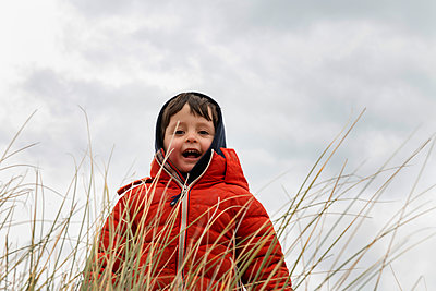 Boy in red puffer jacket behind long grass - p924m2164828 by Bonfanti Diego