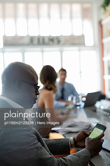 Businessman using cell phone in bar - p1192m2123328 by Hero Images