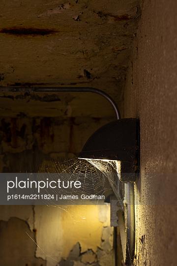 Wandlampe in einem schmutzigen Keller - p1614m2211824 von James Godman
