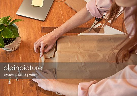 Female freelancer preparing package for delivering at desk in home - p300m2243393 by Veam
