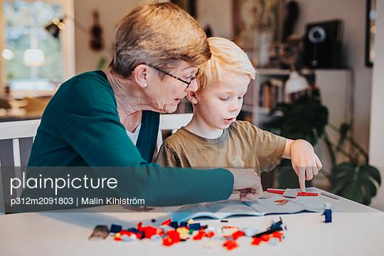 Grandmother and grandson building blocks - p312m2091803 by Malin Kihlström