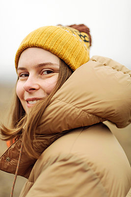 Portrait of young woman smiling outdoors - p1166m2162707 by Cavan Images