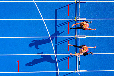 Top view of two female runners crossing hurdles on tartan track - p300m1537358 by Stefan Schurr