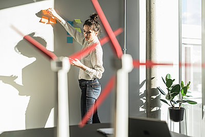 Businesswoman in office putting sticky notes on wall with wind turbine models on desk - p300m2104530 by Uwe Umstätter