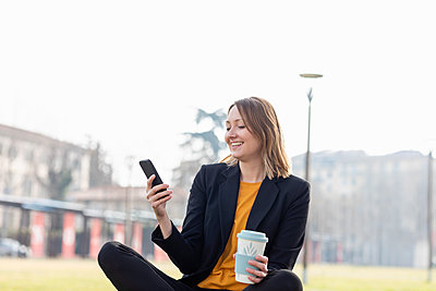 Smiling entrepreneur with disposable cup using mobile phone - p300m2275053 by Emma Innocenti