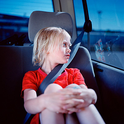 Girl sitting in car, looking through window - p528m1075426f by Johan Willner
