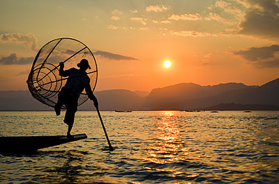 Traditional fisherman balancing on one leg on a boat, holding  fishing basket, fishing on Lake Inle at sunset, Myanmar. - p1100m2164702 by Mint Images