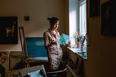 Female artist holding glass pane in her studio - p300m2132308 by Oxana Guryanova