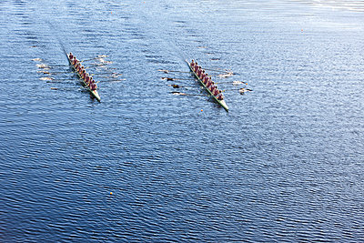 Elevated view of two rowing eights in water - p300m975559f by zerocreatives