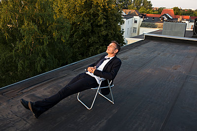 Businessman relaxing on roof - p341m2008659 by Mikesch