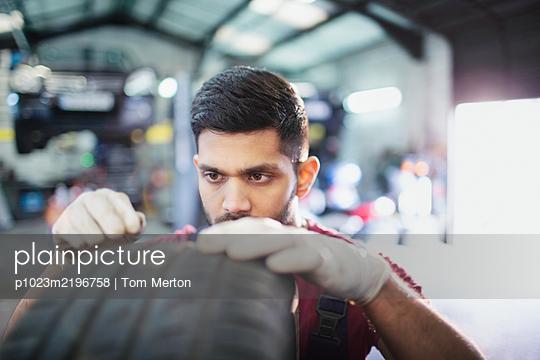 Focused male mechanic examining tire in auto repair shop - p1023m2196758 by Tom Merton