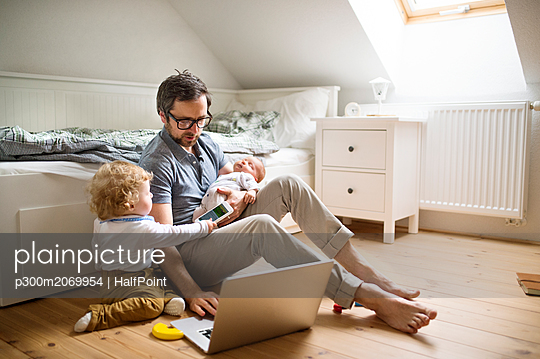 Father with his little son and baby daughter working from home - p300m2069954 by HalfPoint