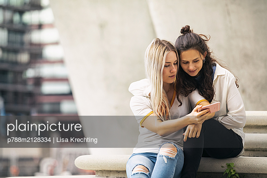 Two young women looking at smartphone - p788m2128334 by Lisa Krechting