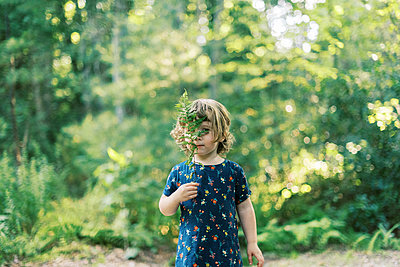 Two year old toddler playing with a fern leaf in the woods - p1166m2205704 by Cavan Images