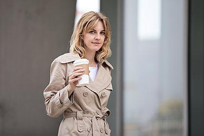 Frau im Trenchcoat mit Kaffeebecher - p788m1466163 von Lisa Krechting