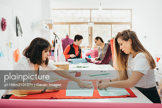 Fashion designers working in the design studio - p1166m2131071 by Cavan Images