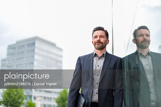 Confident businessman leaning on glass wall of office building with reflection in city - p300m2188376 by Daniel Ingold