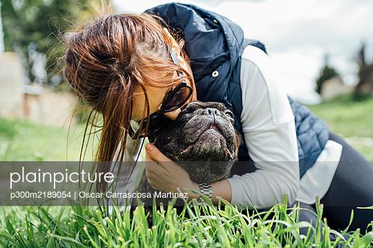 Woman cuddling her bulldog on a meadow - p300m2189054 by Oscar Carrascosa Martinez
