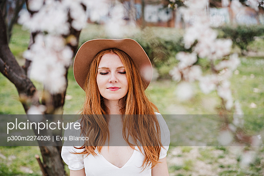 Redhead woman with eyes closed wearing hat at park - p300m2274026 by Eva Blanco