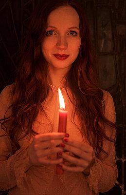 Frau leuchtet mit Kerze - p045m1208220 von Jasmin Sander