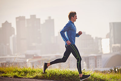 Male runner running on sunny urban street - p1023m1201838 by Ryan Lees
