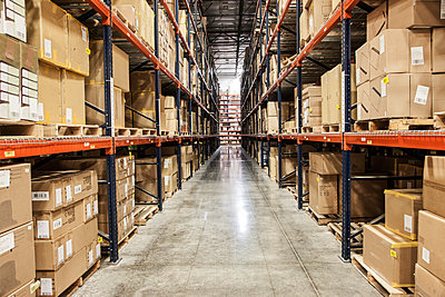 View down an aisle of racks holding cardboard boxes of product on pallets  in a large distribution warehouse - p1100m1575484 by Mint Images