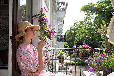 Blonde woman on her balcony - p1678m2258869 by vey Fotoproduction
