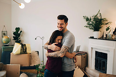 Smiling man embracing woman while standing in living room during relocation - p426m1542777 by Maskot