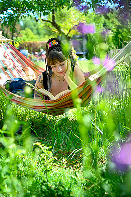 Young woman reading book in a hammock - p427m2203617 by Ralf Mohr