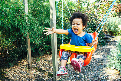 Low angle view of mixed race girl shouting on swing - p555m1421589 by Inti St Clair photography