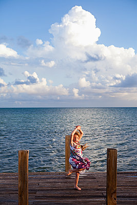 Caucasian girl dancing on pier - p555m1480016 by Marc Romanelli