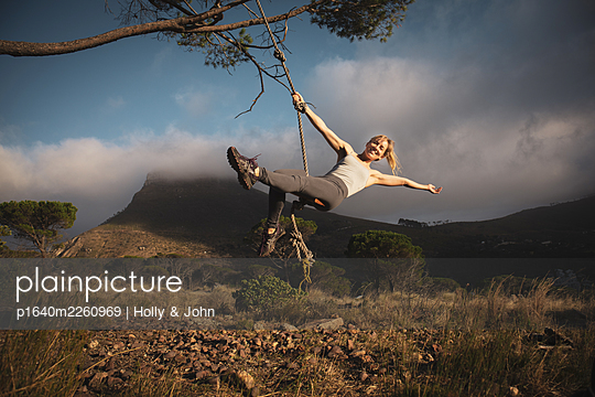 Blond woman swings on a rope in the mountains - p1640m2260969 by Holly & John