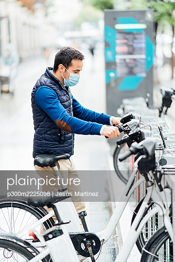 Young man wearing protective face mask holding electric bicycle at parking station during COVID-19 - p300m2225098 by Jesús Martinez