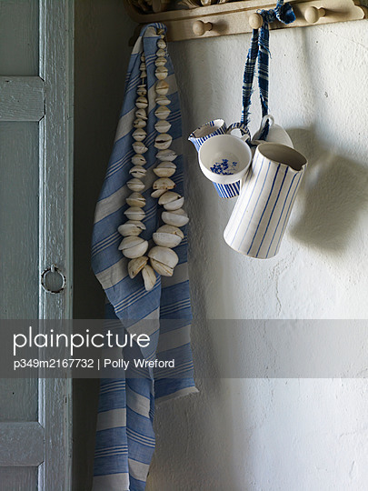 Seashells and dishcloth hang with jugs on hooks, Spain - p349m2167732 by Polly Wreford