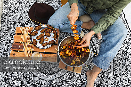 Low section of woman preparing meat skewers for barbecue during vacation - p426m2296384 by Maskot