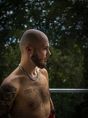 Bare-chested man with tattoos on the balcony - p1267m2258791 by Jörg Meier
