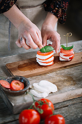 Woman's hands preparing Caprese Salad, partial view - p300m2012400 von Alberto Bogo