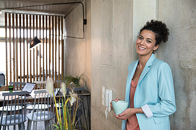 Portrait of smiling businesswoman holding coffee mug at concrete wall in a loft - p300m2079534 by Florian Küttler