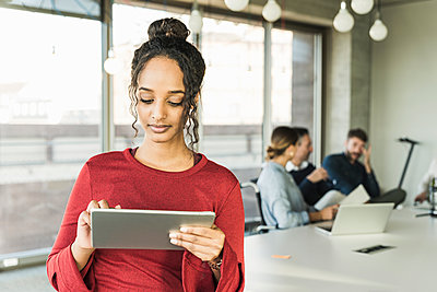 Young businesswoman using tablet during a meeting in office - p300m2160318 by Uwe Umstätter