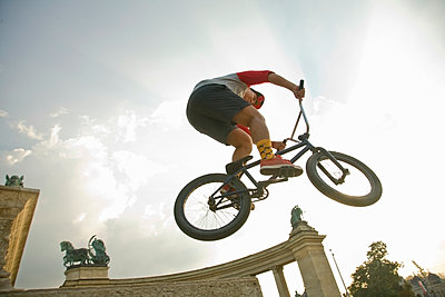 Young man performing stunt on BMX bicycle at Hero's Square, Budapest, Hungary - p300m2225030 by LOUIS CHRISTIAN