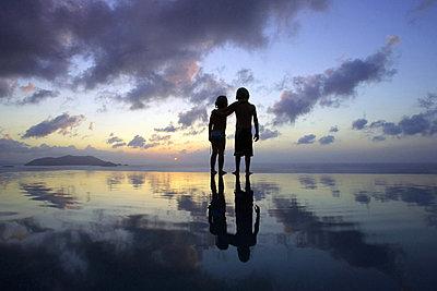 Children standing on beach at sunset - p42915881f by Michael Truelove