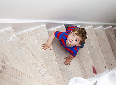 Toddler boy climbing steps - p429m665268f by Nancy Honey