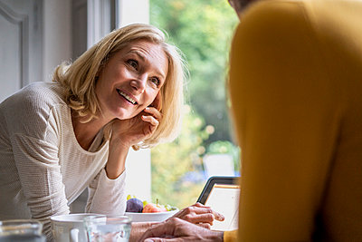 Smiling mature woman looking at her husband while using digital tablet - p623m2271806 by Frederic Cirou